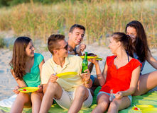Smiling friends sitting on summer beach Stock Photo