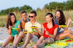 Smiling friends sitting on summer beach Stock Photos