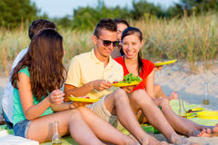 Smiling friends sitting on summer beach Royalty Free Stock Image