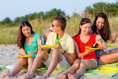 Smiling friends sitting on summer beach. Friendship, happiness, summer vacation, holidays and people concept - group of smiling friends having picnic on beach royalty free stock image