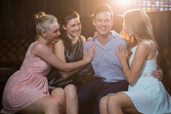 Smiling friends sitting together in sofa. At bar Royalty Free Stock Photo