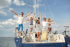 Smiling friends sitting on yacht deck and greeting. Vacation, travel, sea, friendship and people concept - smiling friends sitting on yacht deck and greeting Royalty Free Stock Photo
