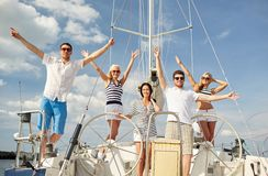 Smiling friends sitting on yacht deck and greeting. Vacation, travel, sea, friendship and people concept - smiling friends sitting on yacht deck and greeting Royalty Free Stock Photography