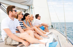 Smiling friends sitting on yacht deck Royalty Free Stock Photo