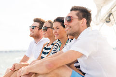 Smiling friends sitting on yacht deck Stock Photography