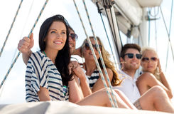 Smiling friends sitting on yacht deck Stock Photo