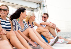 Smiling friends sitting on yacht deck Royalty Free Stock Photos