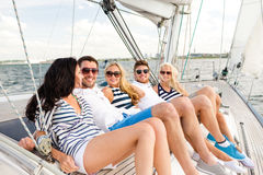 Smiling friends sitting on yacht deck Stock Image