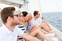 Smiling friends sitting on yacht deck. Vacation, travel, sea, friendship and people concept - smiling friends sitting on yacht deck Stock Image