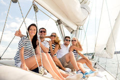 Smiling friends sitting on yacht deck Royalty Free Stock Images