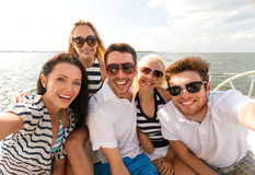 Smiling friends sitting on yacht deck Royalty Free Stock Image