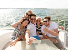 Smiling friends sitting on yacht deck Royalty Free Stock Photography