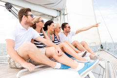 Smiling friends sitting on yacht deck Stock Photos