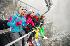 Friends skiers and snowboarders on ski lift for skiing in the mo. Smiling friends skiers and snowboarders on ski lift for skiing in the mountains Stock Photos