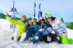 Smiling friends after skiing sit on snow together. Smiling friends after skiing sitting on snow hug and wave hands with ski standing behind Royalty Free Stock Image