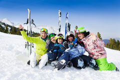 Smiling friends after skiing sitting on snow. Smiling positive friends after skiing sitting on snow hugging and waving hands with ski standing behind Royalty Free Stock Image