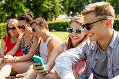 Smiling friends with smartphone making selfie Royalty Free Stock Photos