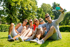 Smiling friends with smartphone making selfie Royalty Free Stock Photo