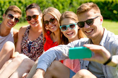 Smiling friends with smartphone sitting on grass Royalty Free Stock Image