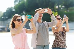 Smiling friends with smartphone taking picture Royalty Free Stock Image