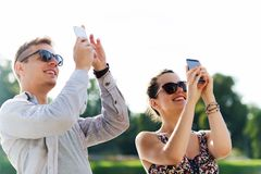 Smiling friends with smartphone taking picture Royalty Free Stock Photography
