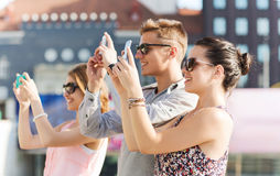 Smiling friends with smartphone taking picture Royalty Free Stock Images