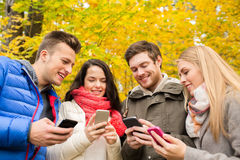 Smiling friends with smartphones in city park Royalty Free Stock Photos