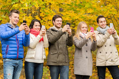 Smiling friends with smartphones in city park Stock Image