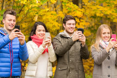 Smiling friends with smartphones in city park Royalty Free Stock Image