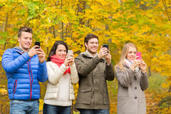Smiling friends with smartphones in city park Royalty Free Stock Photography