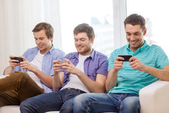 Smiling friends with smartphones at home Stock Photography