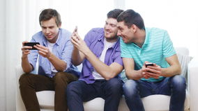 Smiling friends with smartphones at home stock video footage