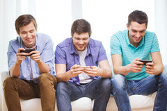 Smiling friends with smartphones at home Stock Photo