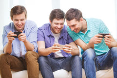 Smiling friends with smartphones at home. Friendship, technology and home concept - smiling male friends with smartphones at home Royalty Free Stock Images