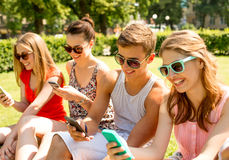 Smiling friends with smartphones sitting on grass Royalty Free Stock Image