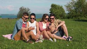 Smiling friends with smartphones sitting on grass stock video footage
