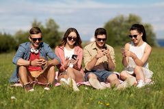 Smiling friends with smartphones sitting on grass royalty free stock photography