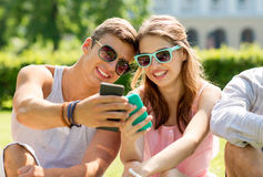 Smiling friends with smartphones sitting in park Royalty Free Stock Photo