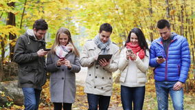 Smiling friends with smartphones and tablet pc stock footage