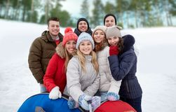 Smiling friends with snow tubes and selfie stick Royalty Free Stock Photos