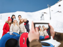 Smiling friends with snow tubes and tablet pc Royalty Free Stock Photos