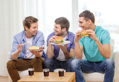 Smiling friends with soda and hamburgers at home Stock Images