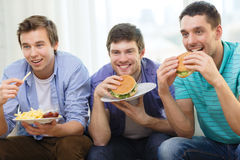 Smiling friends with soda and hamburgers at home Royalty Free Stock Photos