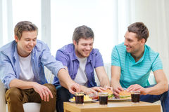 Smiling friends with soda and hamburgers at home Royalty Free Stock Images