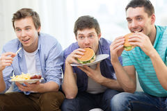 Smiling friends with soda and hamburgers at home Royalty Free Stock Photo