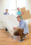 Smiling friends with sofa and boxes at new home Royalty Free Stock Photography