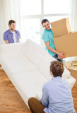 Smiling friends with sofa and boxes at new home Royalty Free Stock Image