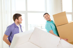 Smiling friends with sofa and boxes at new home Stock Image