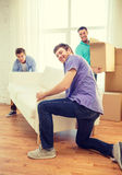 Smiling friends with sofa and boxes at new home Royalty Free Stock Photos