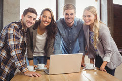 Smiling friends standing around laptop Stock Photos